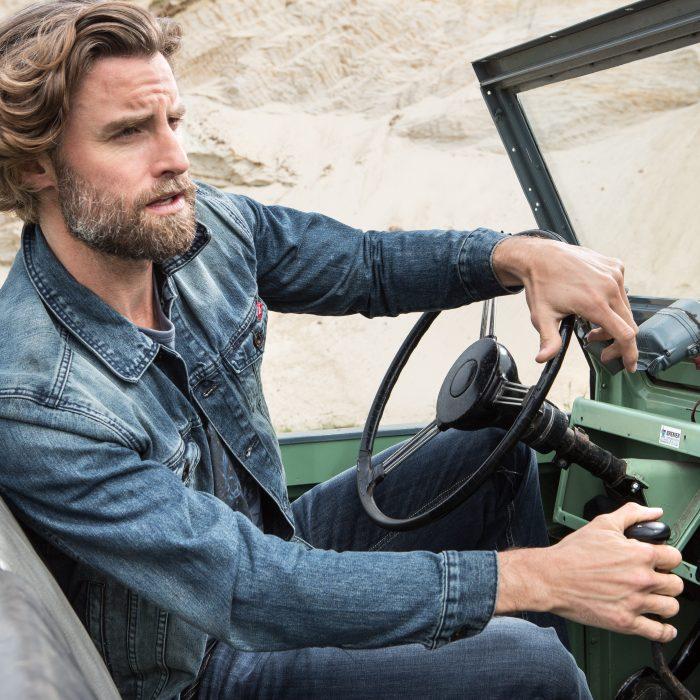 Mann in Jeanskleidung fährt mit Geländwagen durch Wüste