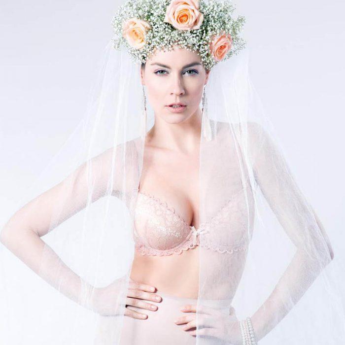 Frau mit floralem Kopfschmuck mit Schleier in Dessous