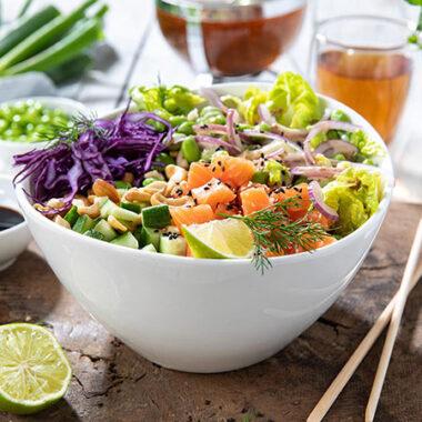 Lachsbowl mit Salat, Rotkohl, Limette, Gurke und Cashewnüssen